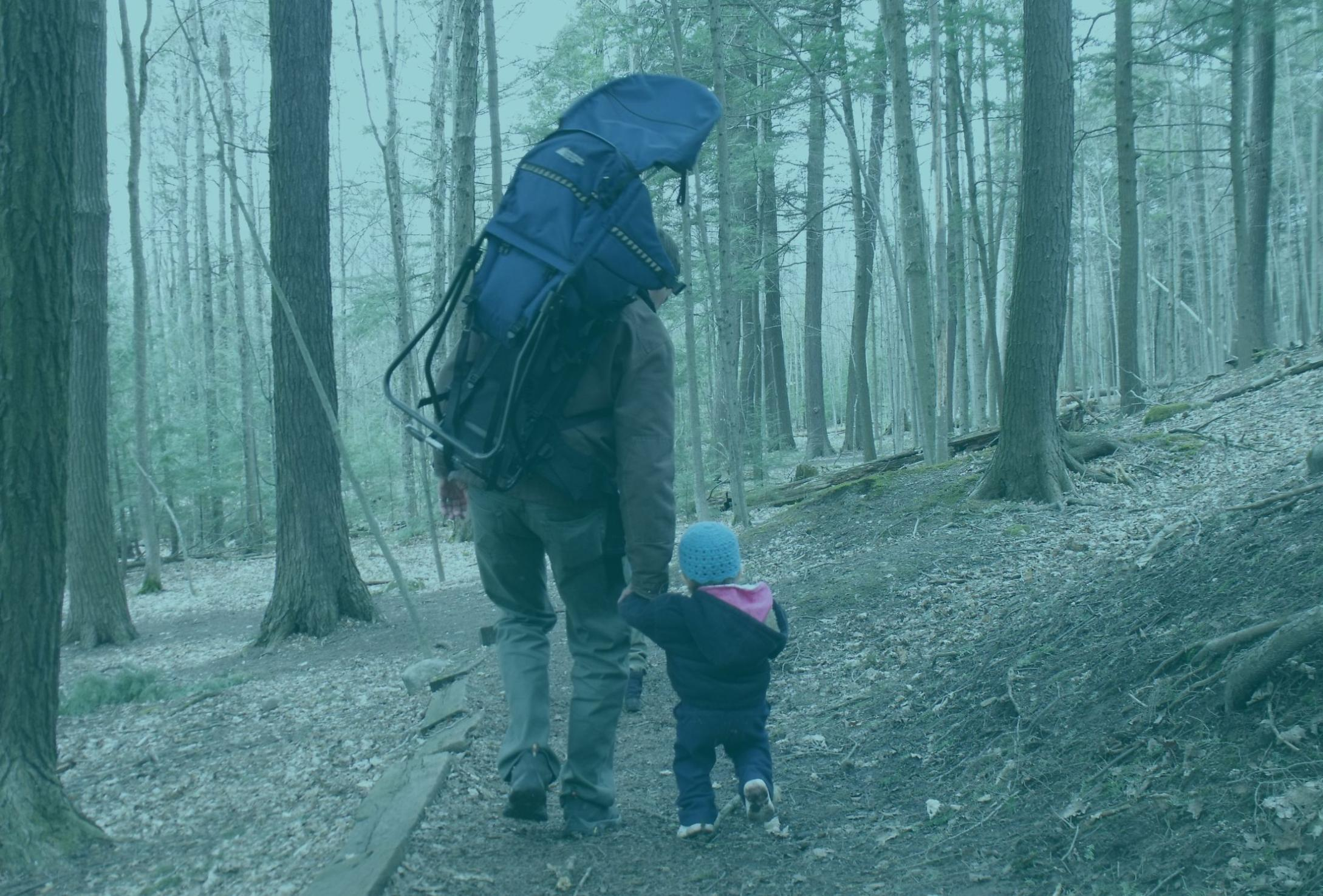 parent and child walking in the woods