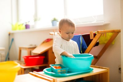 toddler-child-plays-with-water-in-a-basin-DQEBXK5